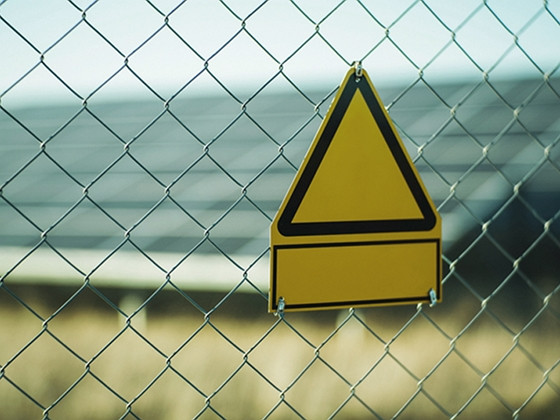 a chain link fence with a yellow triangle sign hanging on it