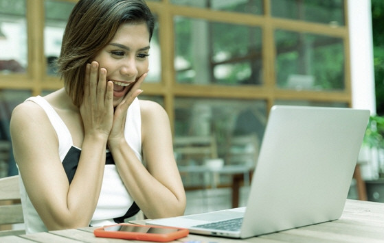 a happy woman in front of a laptop